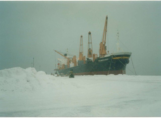 Snow piled on the dock while a ship is loaded.