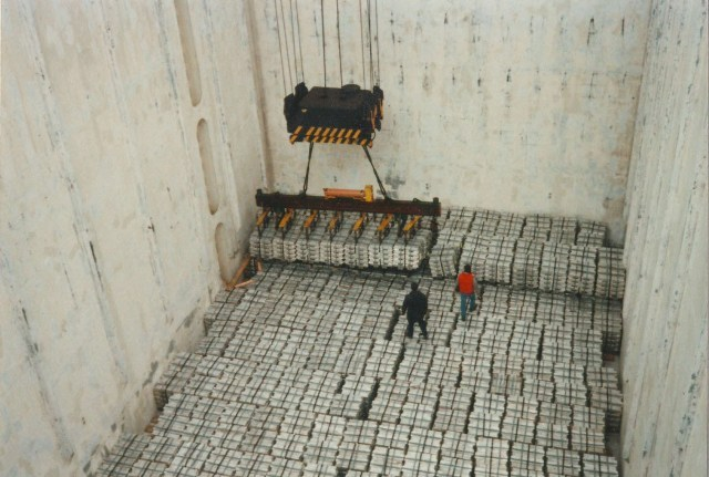 Two stevedores secure aluminum ingots in the hold of a ship.