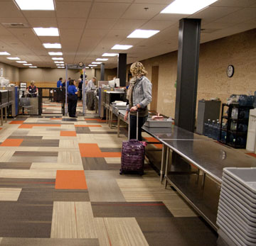 passengers go through the new security checkpoint at the airport